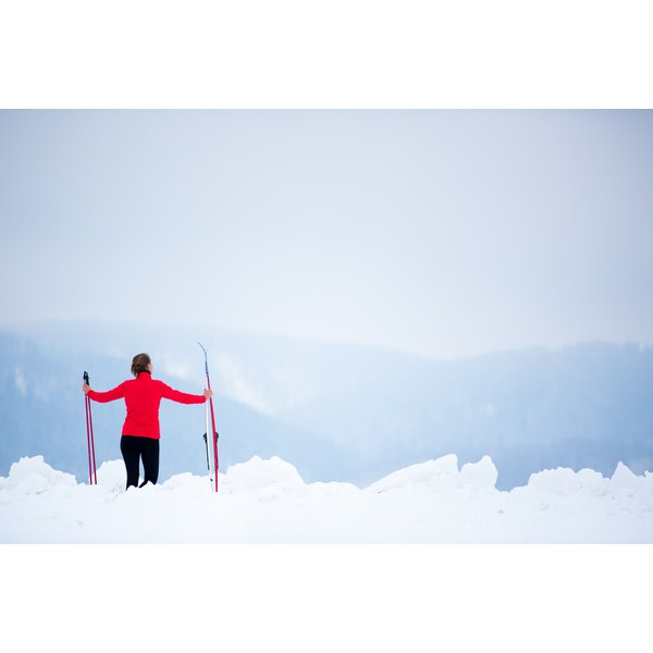 A young woman is holding her cross country skis up.