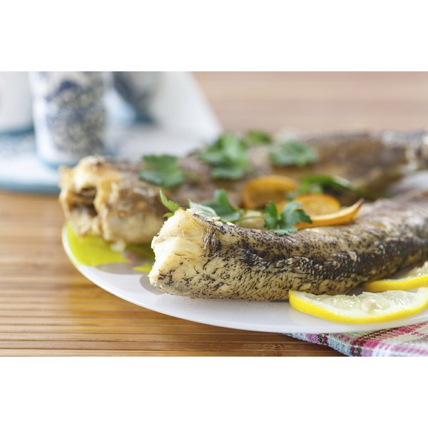 A whole baked fish on a dish with lemon.