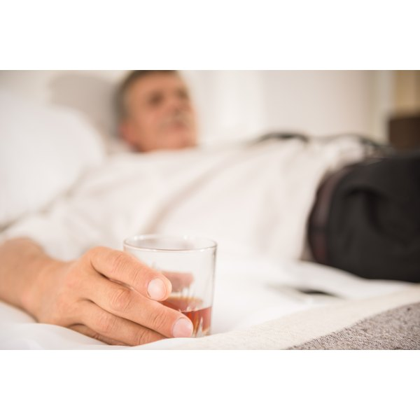 A man relaxing on the bed with a shot of liquor.