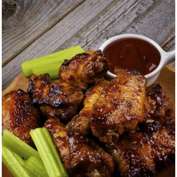 A plate of buffalo wings, celery and dipping sauce.