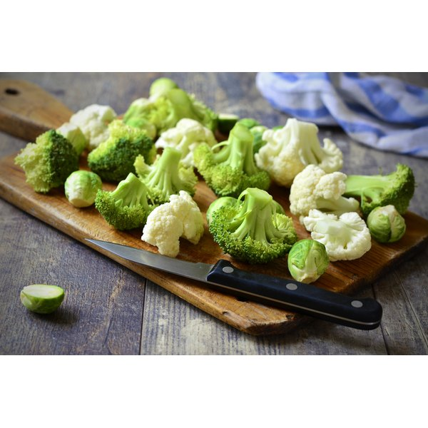 A cutting board with a knife on it with Brussels sprout, cauliflower and broccoli.