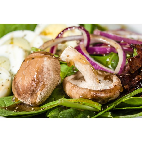 A spinach salad with mushrooms on top.