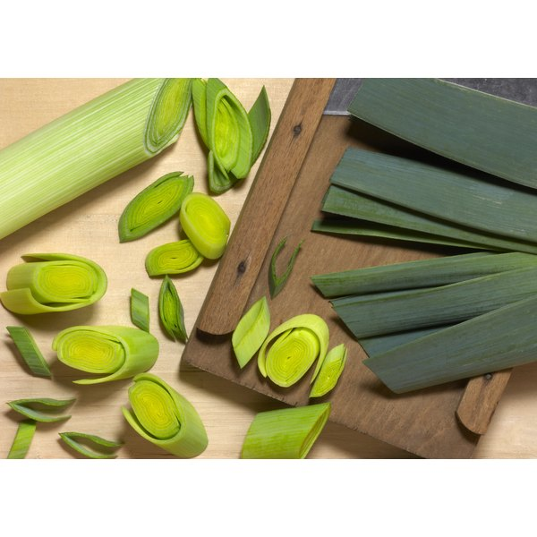 An overhead view of leeks being sliced on a mandoline.