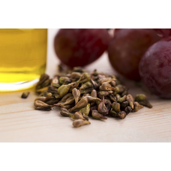 Grape seed oil next to grape seeds and grapes.