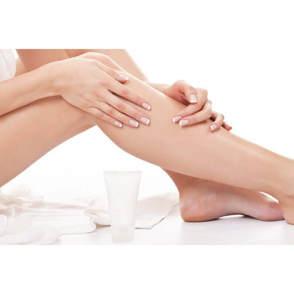 A woman is applying lotion to her legs.