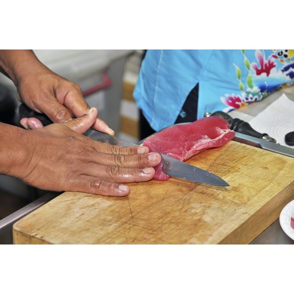 A man cutting fresh red tuna on a cutting board.