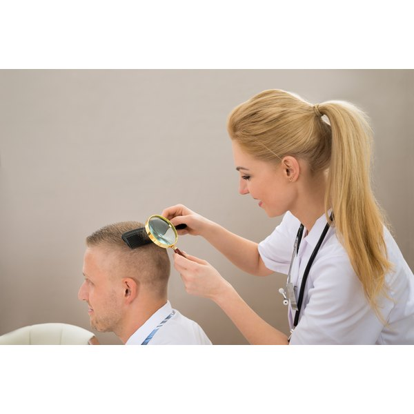 A dermatologist is looking at a patient's hair.