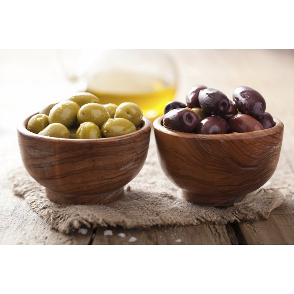 Bowls of olives on a wooden table.