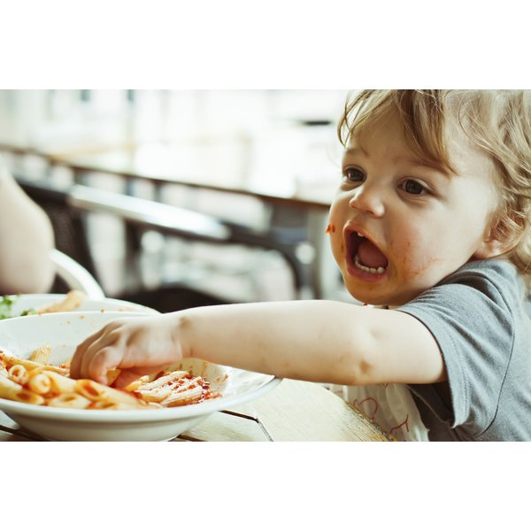 A toddler eating pasta and sauce with his hand.