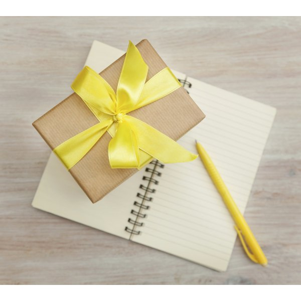 A giftbox sitting on an open notebook with a pen.