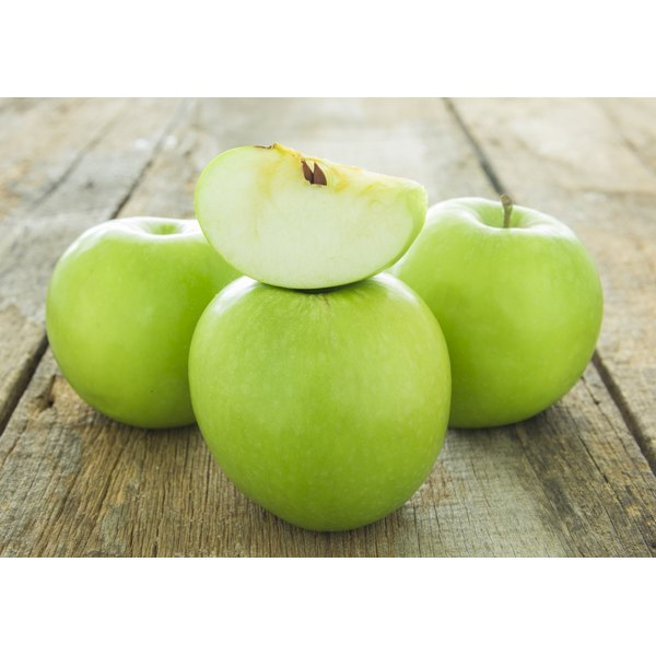 A slice of green apple on a rustic table with three apples.
