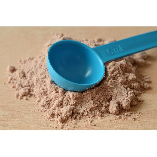 A blue measuring spoon sits in a pile of chocolate whey powder on a wooden table.