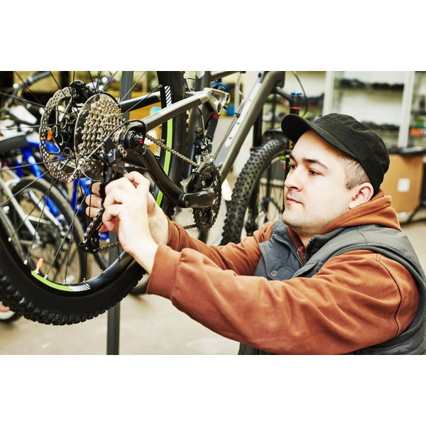 A bike mechanic is working on a chain.
