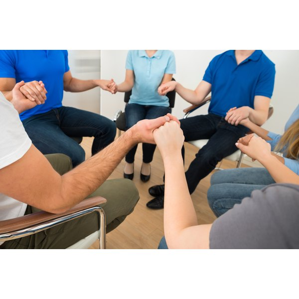 A family holding hands in a circle during a therapy session.