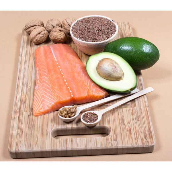 A cutting board with fish, avacado, nuts and seeds.