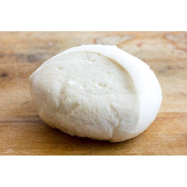 A ball of fresh mozzarella on a cutting board.