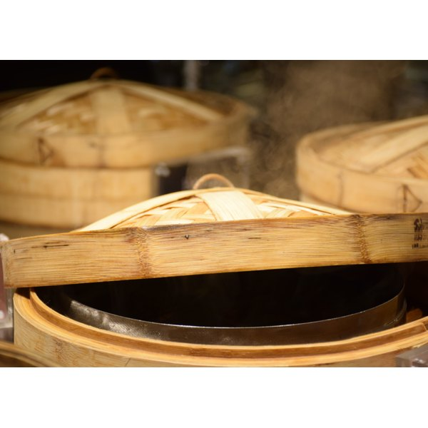A group of bamboo steamers, one with the lid a little bit open.