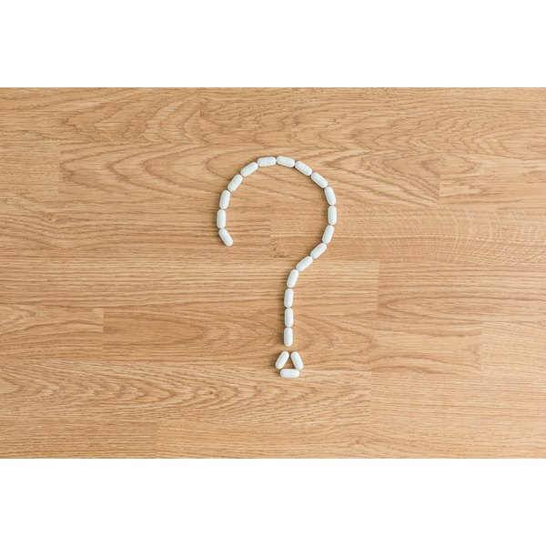 White caplets on a table in the shape of a question mark.