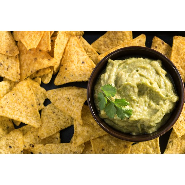 A bowl of guacamole with chips.