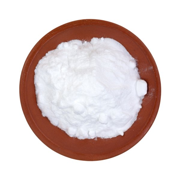 A plate containing baking soda sits on a table.