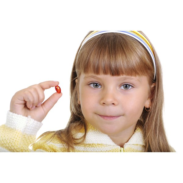 A child holds up a vitamin between her fingers.