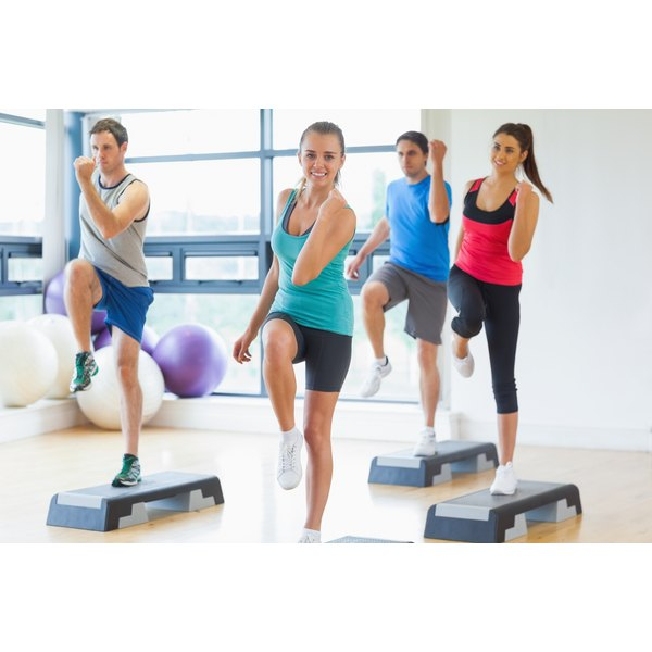 A group of people are training in an aerobics studio.