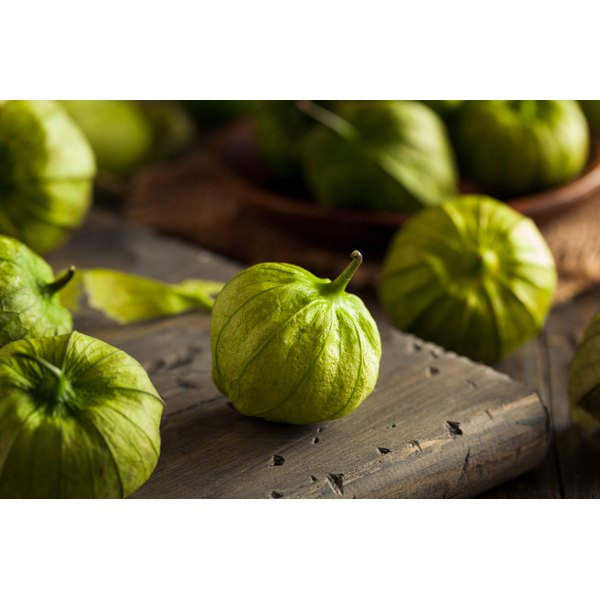 Green tomatillos on a wooden table.