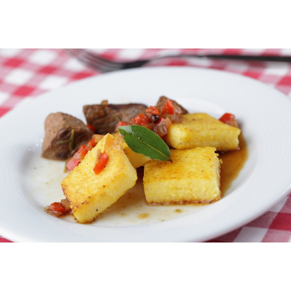 Polenta, here as firm squares, can taste bitter when cooked if it's stored too long.