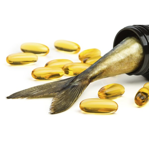 Fish oil tablets and a fish tail in jar.