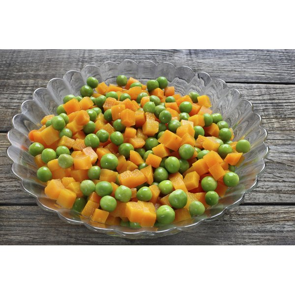 A glass dish of peas and carrots on a rustic table.