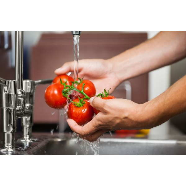 A woman is washing tomatoes.