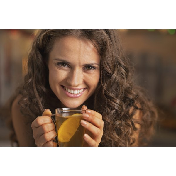 A young woman holding a cup of ginger herbal tea.