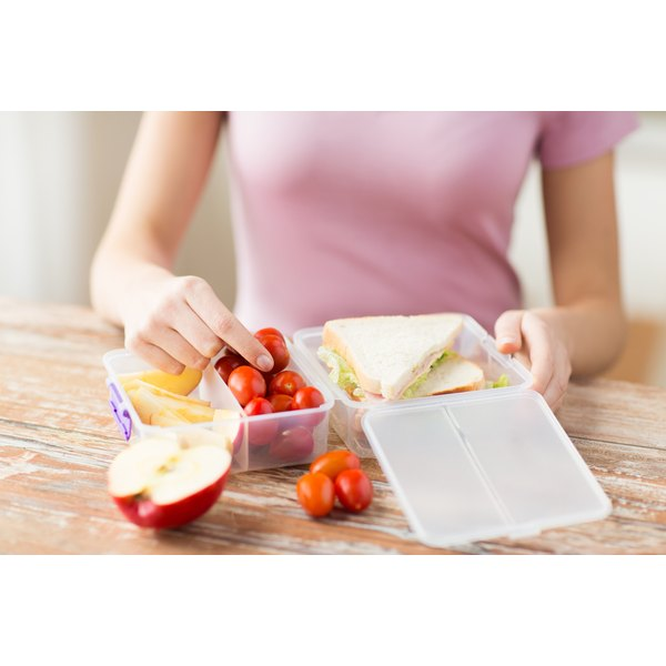 A close-up of a teenage girl packing a healthy lunch.