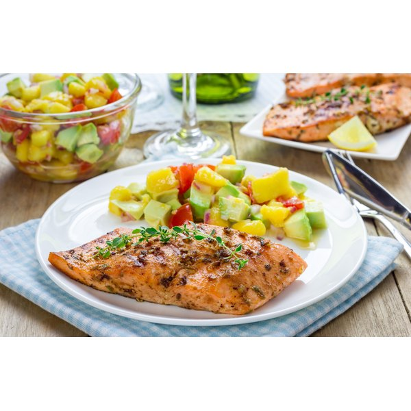 A plate with grilled salmon and mango avocado salsa.