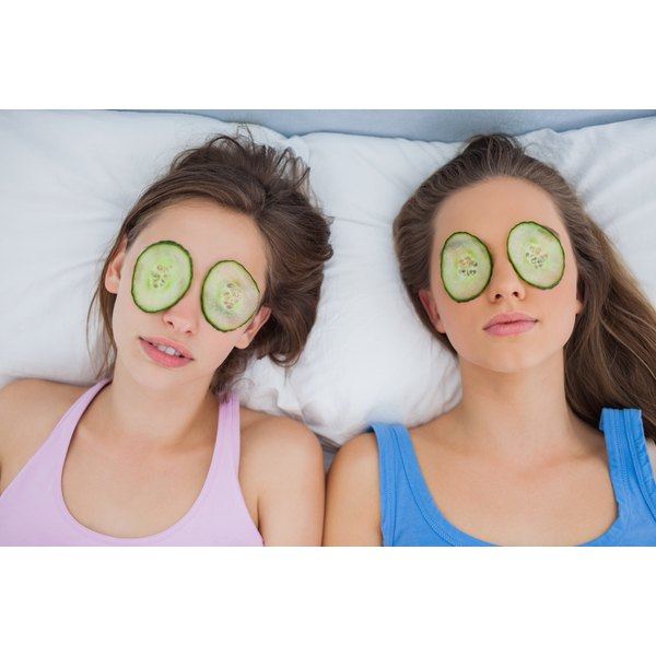 Girls in bed with cucumbers over their eyes