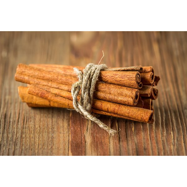 A bundle of cinnamon sticks tied up with string on a wooden table.