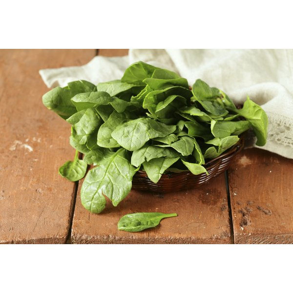 Fresh basket of spinach on a wooden table.