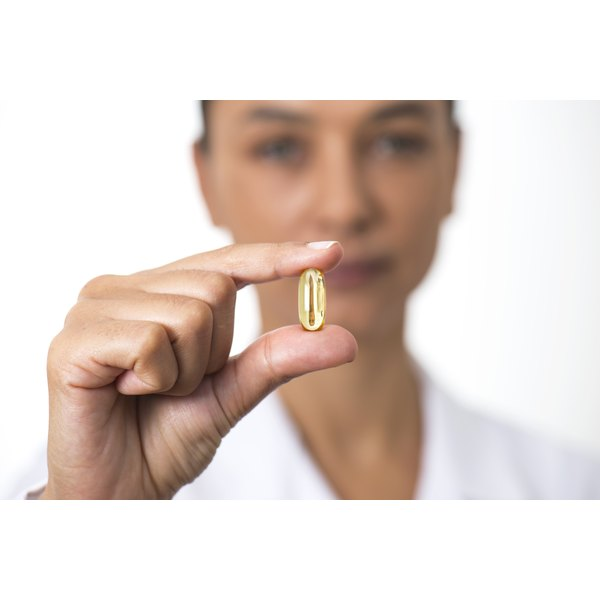 A woman is holding a fish oil pill in her hand.