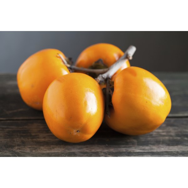 Ripe persimmons on a wooden table.