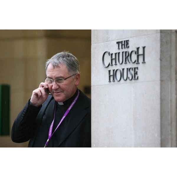 The Rev Canon Glyn Webster uses his phone Nov. 21, 2012, outside Church House in London.