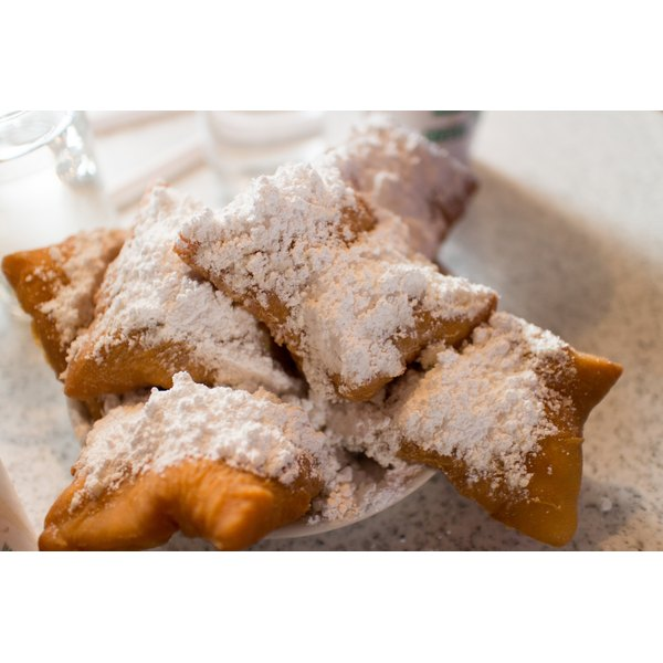 A plate of beignets with powdered sugar.