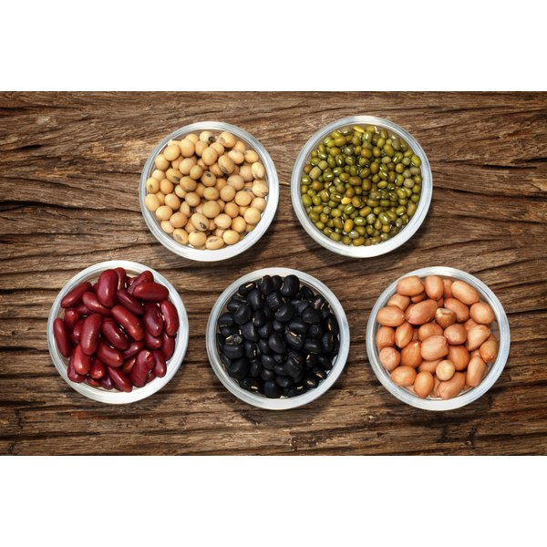 Various beans in bowls on a wooden table
