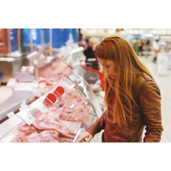 A young woman shops for meat at the butcher shop counter.