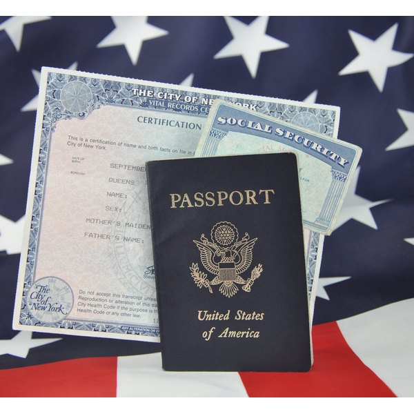 A birth certificate along with a passport and social security card sit atop a US flag.