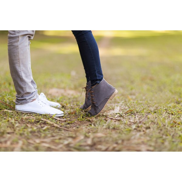Close-up of a teenage couples' feet as they face each other kissing in a park.