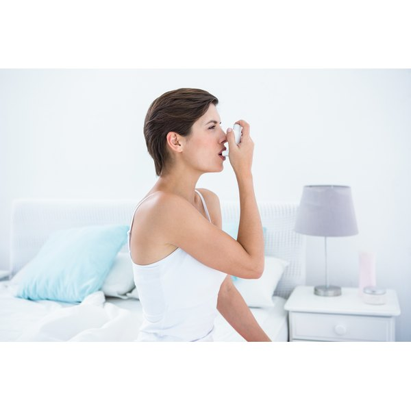 Woman sitting on a bed using an asthma inhaler