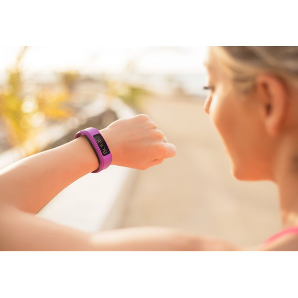 A female runner is looking at her fitness tracker.