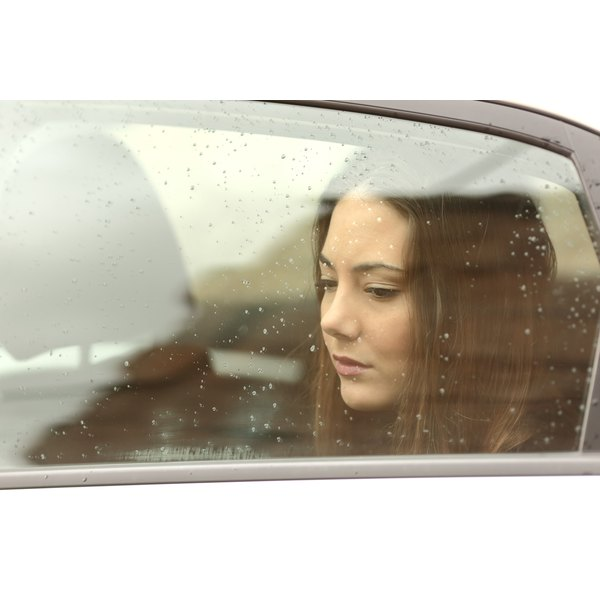 Sad woman looking through a car window on a rainy day.