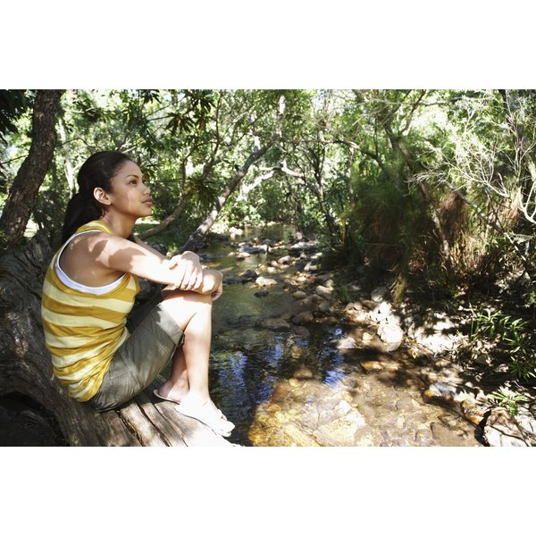 Preteen girl sitting by a creek taking a break during a hike.