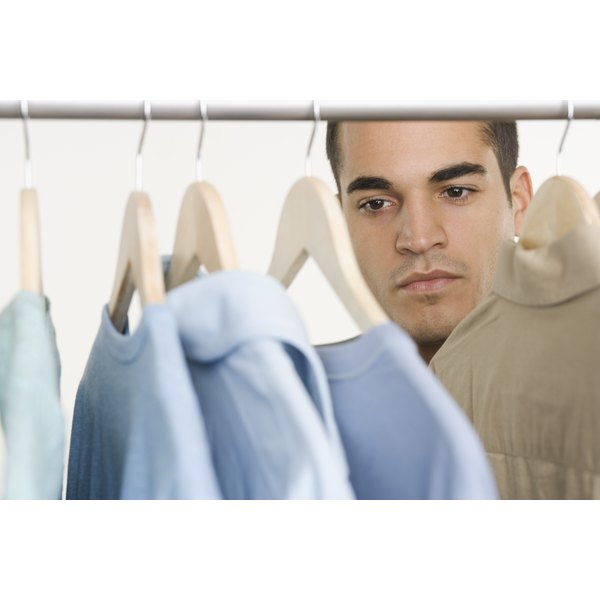 Man looking at his shirts in the closet